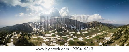 Panoramic view of mountains in Switzerland during spring with blue skies, snow and pine trees taken from a drone