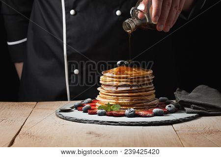 The Chef Pours Maple Syrup On Pancake Stack With Blueberries And Strawberries On Black Background.