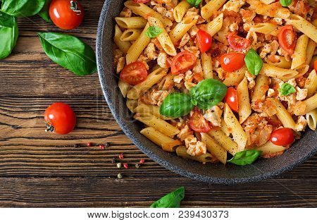 Penne Pasta In Tomato Sauce With Chicken, Tomatoes, Decorated With Basil On A Wooden Table. Italian
