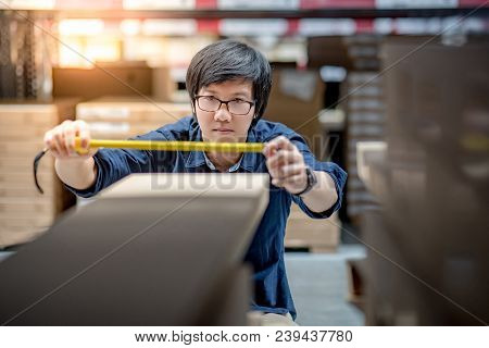Young Asian man using tape measure for measuring dimension of product in cardboard box. Shopping lifestyle in warehouse concept poster