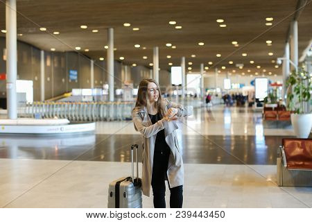 Female Tourist Wearing Grey Coat Walking In Airport Hall With Valise And Looking At Watch. Concept O