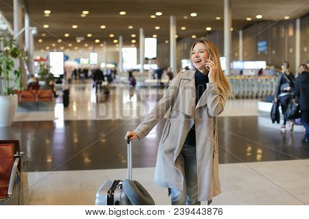 Caucasian Woman Talking By Mobile Phone And Going With Grey Valise In Airport Waiting Room. Concept