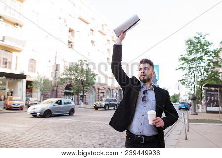 A Business Man With Documents And A Cup Of Coffee In His Hands Catches A Taxi Near The Road. A Man I