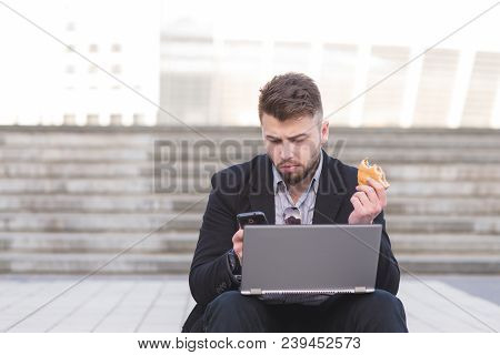 Busy Man Is Sitting On A Staircase With A Laptop And Snack And Uses A Smartphone. A Busy Businessman