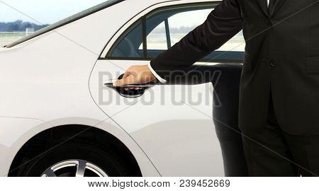 Chauffeur In Black Suit Opening Car Door