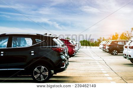 Luxury Black, White And Red New Suv Car Parked On Concrete Parking Area At Factory With Blue Sky And