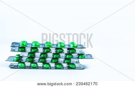 Stacks Of Green Round Sugar-coated Tablet Pills In Blister Packs On White Background With Copy Space
