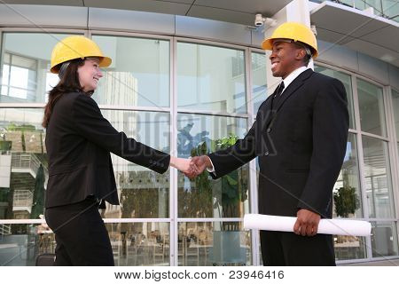 A handsome architect meeting with a client at the worksite