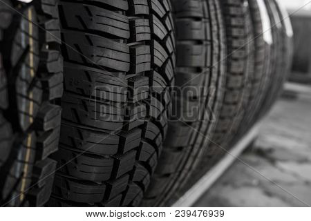 poster of Protector of automobile tires. A number of automobile tires. Close up view on auto mobile new wheel tire surface. Different pattern and type tires for car industry commercial transport transpotration