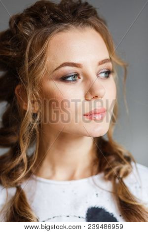 Brunette Girl On Gray Background Looking To The Side.