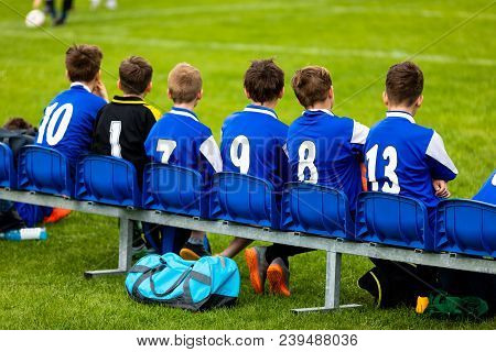 Kids Soccer Team On A Bench. Children Football Team Players. Young Boys In Blue Jerseys As A Substit