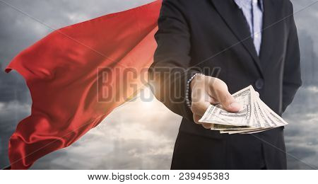 Confident Business Superhero Man Wearing Red Cape Against Holding Dollar Money With City Background.