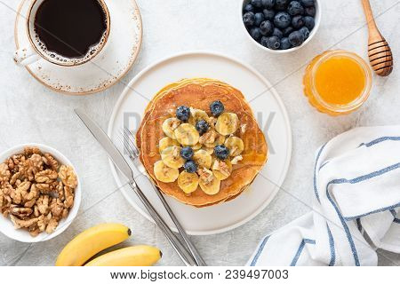 Top View Of Tasty Breakfast Pancakes With Honey And Blueberries. Pancakes Breakfast. Banana Pancakes
