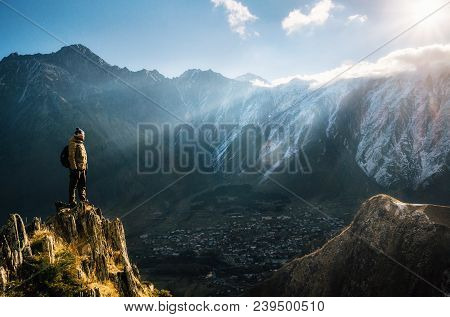 Backpacker Sit On Cliff Edge And Looks At Mount Valley