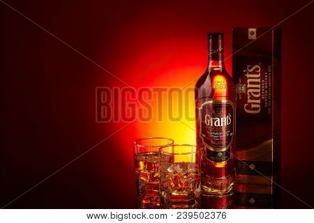 Bottle of Grant's whisky and two glasses with whisky and ices on a red background with yellow ligthing. Copy space.