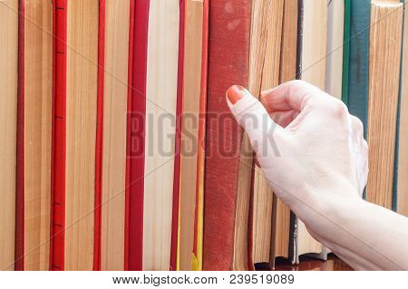 Female Hand Is Taking An Old Book From The Bookshelf. Many Hardback Books On Wooden Shelf. Education