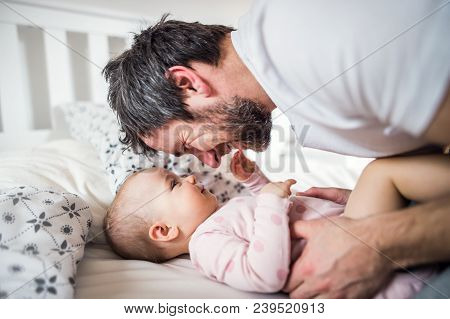 Father With A Toddler Girl On Bed At Home At Bedtime. Paternity Leave.