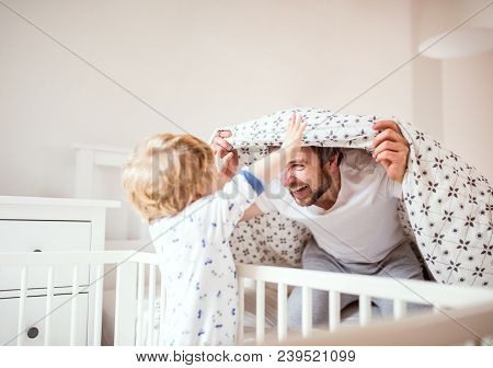 Father With A Toddler Boy Having Fun In Bedroom At Home At Bedtime. Paternity Leave.