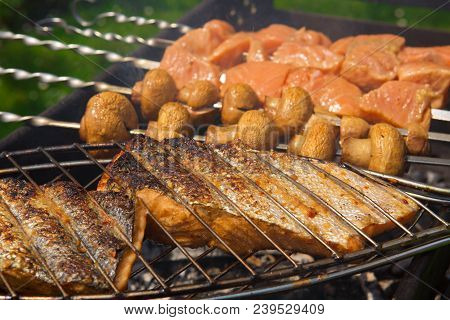 Grilled Salmon Steaks On The Grill. Portobello Mushrooms Marinated And Grilling Close Up.