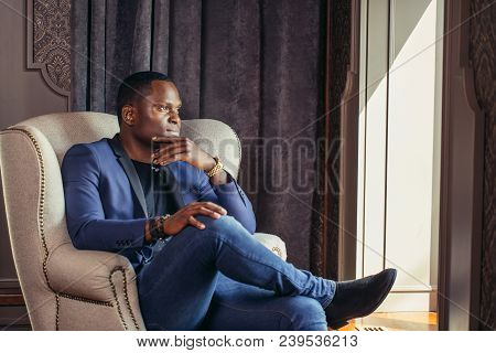 Dark-skinned Middleaged Adult Thinking About His Job Comfortably Sitting Before The Window