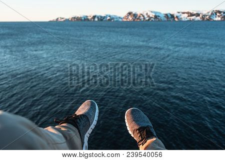 Travel And Lifestyle Concept. Brave Traveler Hipster Sits On Cliff In Front Of Ocean And Mountain