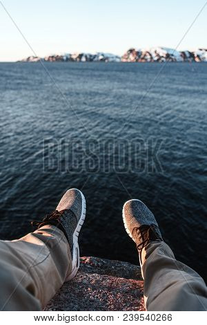 Travel And Lifestyle Concept. Brave Traveler Hipster Sits On Cliff In Front Of Ocean And Mountain. P
