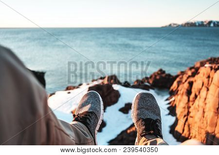 Pov View Of Legs And Shoes On Background Of Snow Rock And Ocean. Brave Explorer Sits In Front Of Sno
