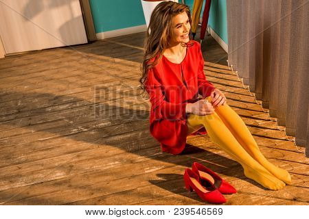 High Angle View Of Smiling Retro Styled Woman In Red Dress Sitting On Floor And Looking At Jalousie