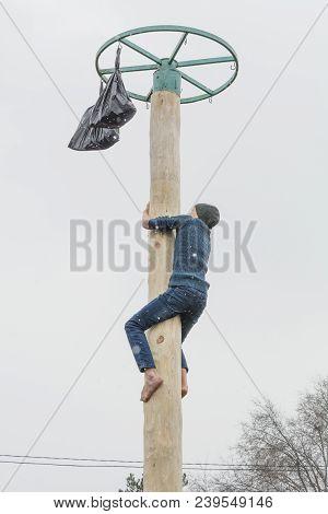 Tiraspol, Moldova-february 18, 2018: Boy Climbing On A Wooden Pole For The Prize. Slavonic Folk Paga
