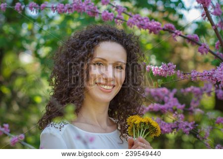 Happy cheerful young woman with curly hair and joyful and charming smile with bunch of dandelions enjoy nature.