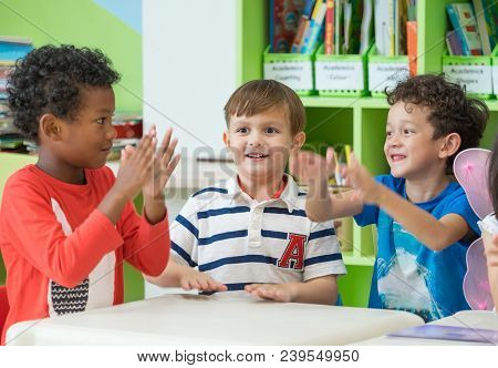 Group Of Diversity Kids Boy Sit On Table And Playing Together In Preschool Library,kindergarten Scho