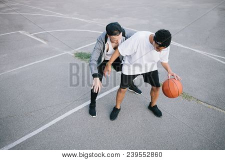 Two Teenagers Are Playing Basketball. The Boy From The Back Is Trying Take Back The Ball While The A