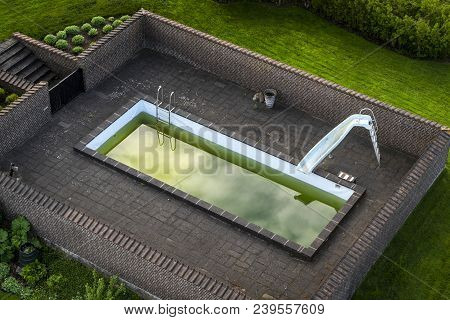 Terrace With A Swimming Pool With Green Water Surrounded By A Brick Wall On A Green Lawn
