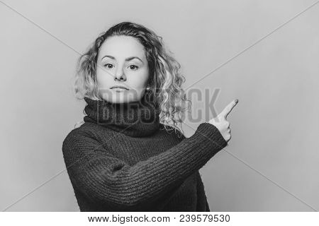 Check This Out. Serious Blonde Young Woman With Curly Blonde Hair Dressed In Bright Blue Sweater, In