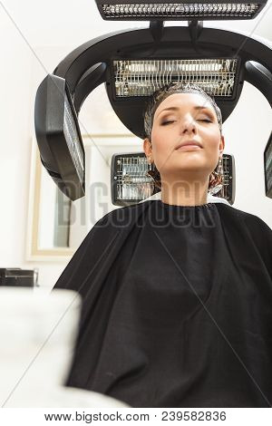 Haircare, Relaxation And Hairstyling Concept. Woman Sitting In Black Cape Getting Her Hair Dried Und