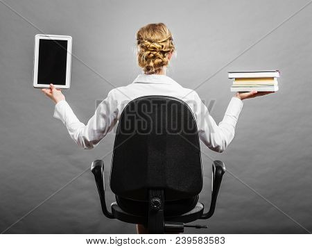 Ebook Vs Book. Woman Sitting On Chair Holding Traditional Book And E-book Reader Tablet Touchpad Pc