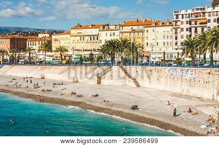 Nice, France - October 13, 2009: People Swimming In Turquoise Sea And Relaxing On Beach That Stretch