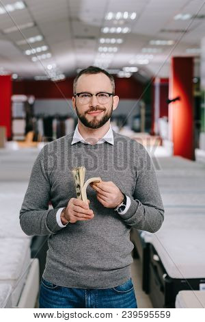 Portrait Of Smiling Male Shopper In Eyeglasses With Dollar Banknotes In Furniture Store