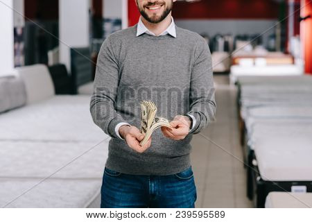 Cropped Shot Of Smiling Male Shopper With Dollar Banknotes In Furniture Store