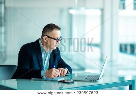 Shot of a senior financial businessman sitting at his workstation in front of computer and laptop while doing some paperwork. poster