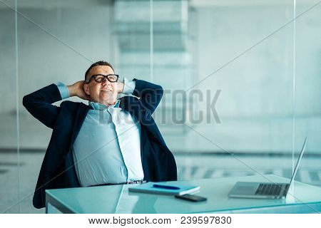 Portrait Of Relaxed Senior Manager Sitting At Office