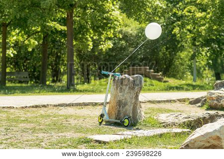 Folding Scooter Leaning Against A Large Stone In The Park. The White Balloon Filled With Helium Tied