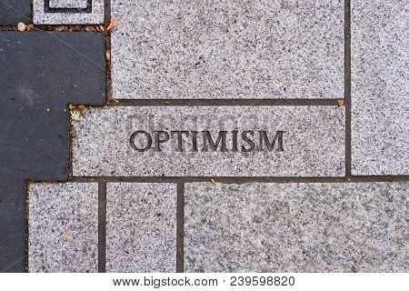 The Word Optimism On A Motivational Brick Sidewalk Made Of Concrete And Mortar.
