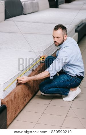 Male Shopper Measuring Orthopedic Mattress With Measure Tape In Furniture Store