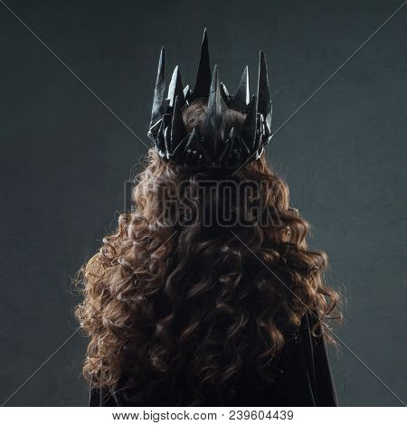 Portrait Of A Gothic Princess. Beautiful Young Brunette Woman In Metal Crown And Black Cloak. Back V