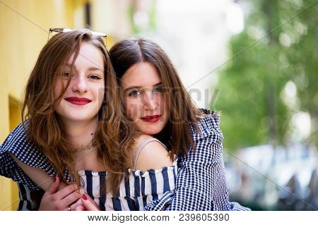 Two lovely young woman having fun on the street. BFF conception.