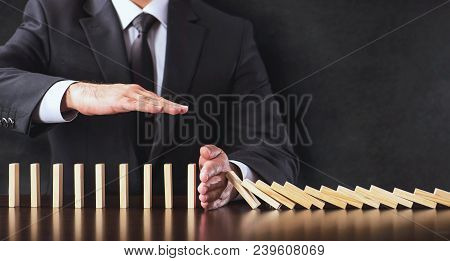 Chain Reaction In Business Concept, Businessman Intervening  Dominos Continuous Toppling And Protect