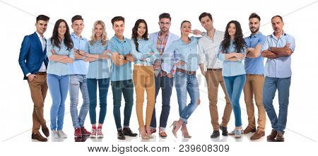 large group of confident work colleagues posing together while standing on white background. They are wearing blue and white shirts and they are also having a senior member in the group
