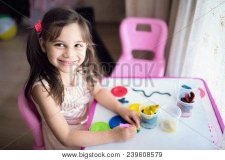 Little Girl Is Playing With Putty At Home