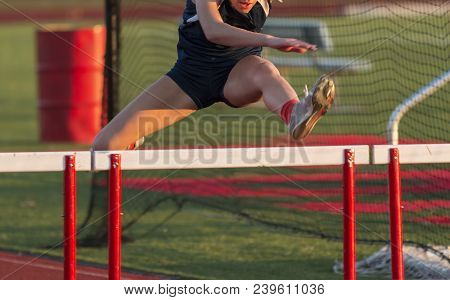 A High School Girl Is Running The Hurdles During A Track And Field Competition Outdoors On A Sunny A
